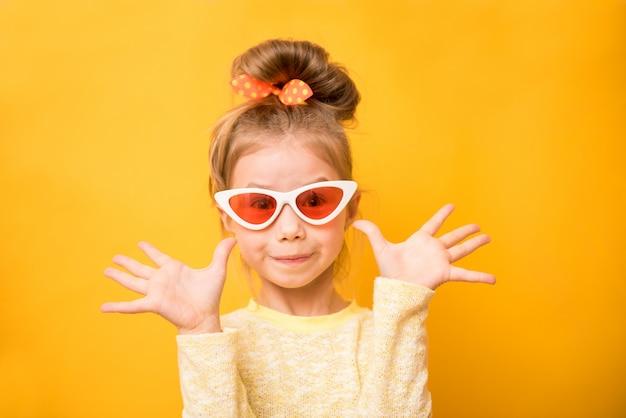Menina engraçada surpresa com óculos escuros de mãos levantadas e olhando a câmera sobre o amarelo