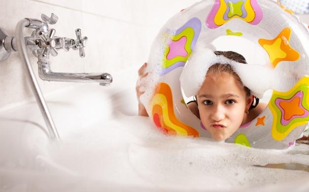 Menina engraçada tomando banho em uma banheira com uma bóia salva-vidas inflável