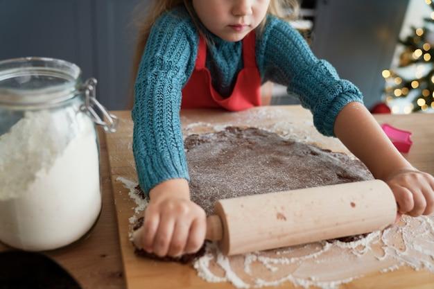 Menina enrolando massa de pão de gengibre para biscoitos caseiros