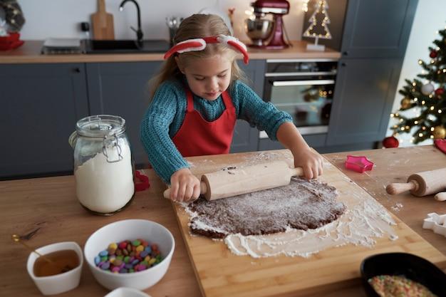 Menina enrolando um pão de gengibre