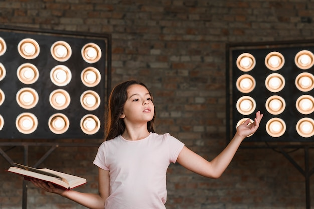 Menina ensaiando contra a parede de tijolos com luz de palco