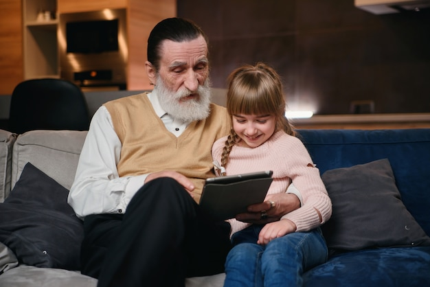 Menina ensina vovô a usar modernos dispositivos inteligentes. comunicação de geração jovem e sênior. aproveite o tempo de lazer com a família.