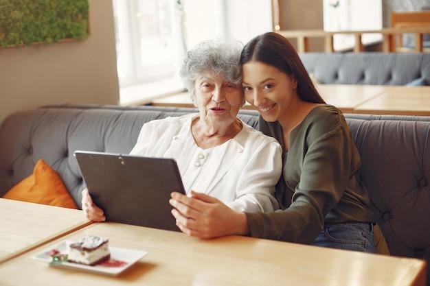 Menina ensinando a avó como usar um tablet