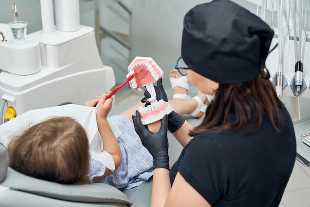 Menina ensinando a escovar os dentes no modelo de dentes.