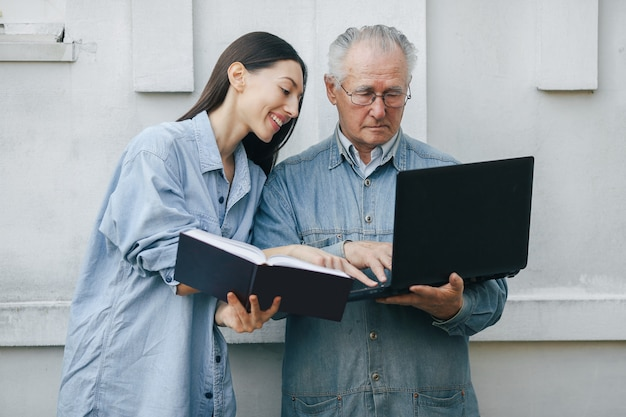 Menina ensinando seu avô como usar um laptop