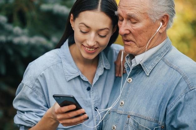 Menina ensinando seu avô como usar um telefone