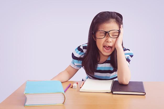 Menina entediada e cansada estudante asiática fazendo lição de casa, isolada no fundo cinza