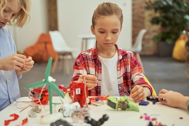 Menina entusiasmada parecendo concentrada enquanto monta um kit de brinquedo eletrônico sentada