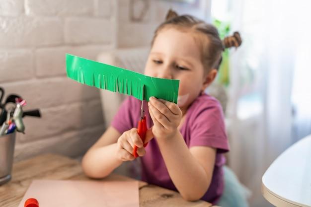 Menina entusiasticamente corta papelão colorido com uma tesoura