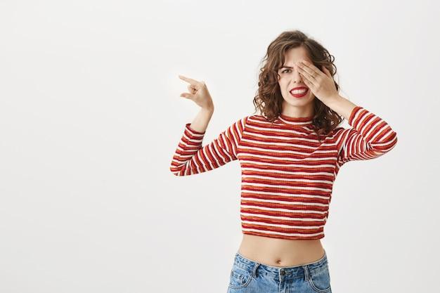 Menina envergonhada fechando os olhos e mostrando algo pequeno com uma careta de decepção