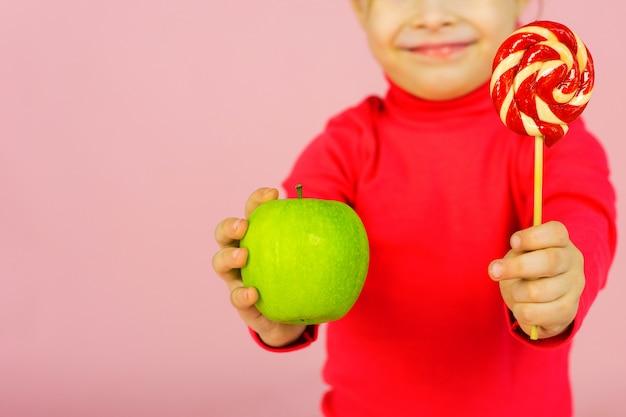 Menina escolhe entre um pirulito e uma maçã verde. o conceito de nutrição adequada. uma criança em uma parede rosa tem um doce de açúcar na mão e uma maçã. dificuldade de escolha