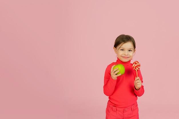 Menina escolhe entre um pirulito e uma maçã verde. o conceito de nutrição adequada.