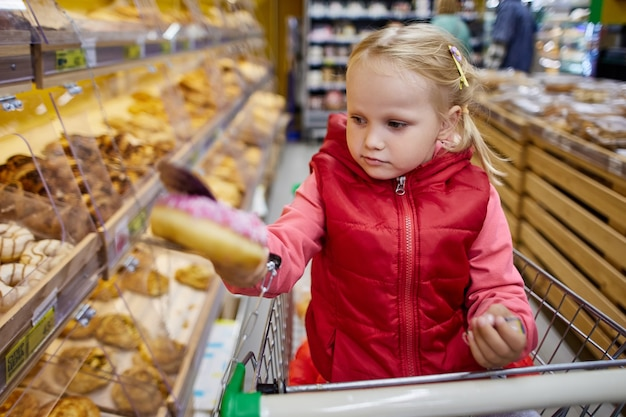 Menina escolhe pastéis no supermercado