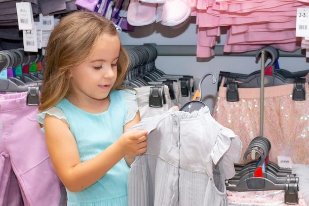 Menina escolhe roupas em uma loja de roupas. olhando para o preço