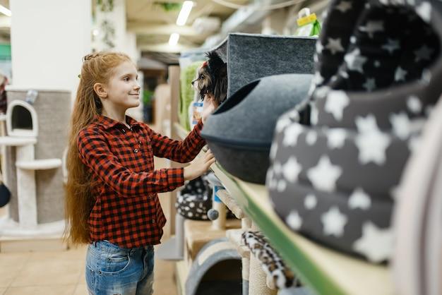 Menina, escolhendo a casinha de cachorro para seu cachorro, loja de animais. criança comprando equipamentos em petshop, acessórios para animais domésticos