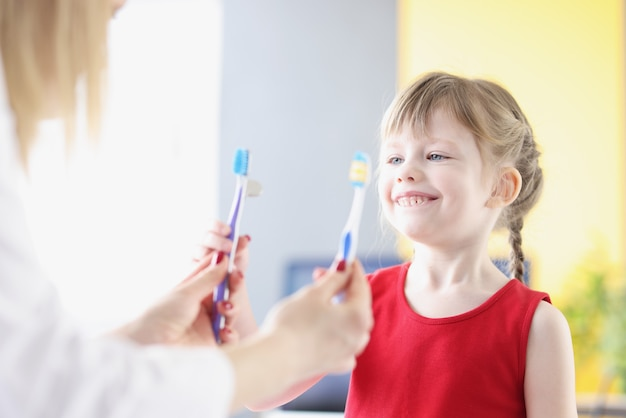 Menina escolhendo escova de dente no dentista na clínica