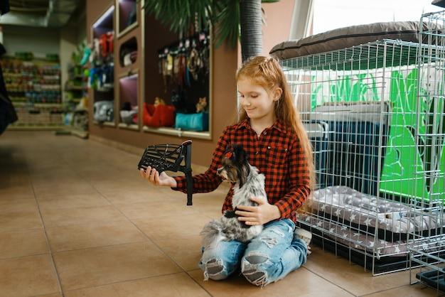 Menina escolhendo focinho para seu cachorro, pet shop. criança comprando equipamentos em petshop, acessórios para animais domésticos