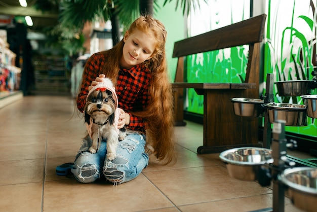 Menina escolhendo roupas para seu cachorro na loja de animais. criança comprando equipamentos em petshop, acessórios para animais domésticos