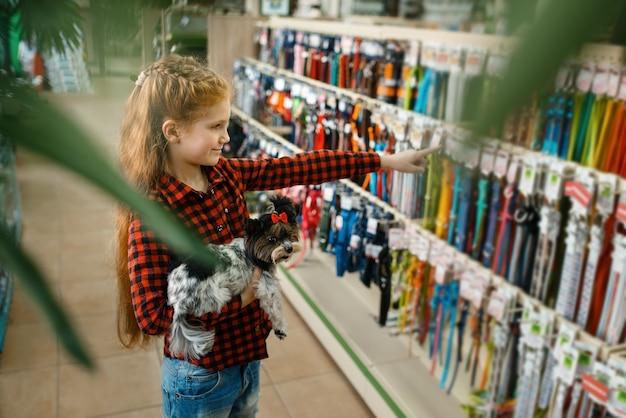 Menina escolhendo trela e coleira para seu cachorro, loja de animais. criança comprando equipamentos em petshop, acessórios para animais domésticos