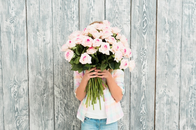 Menina, escondendo o rosto por buquê de rosas