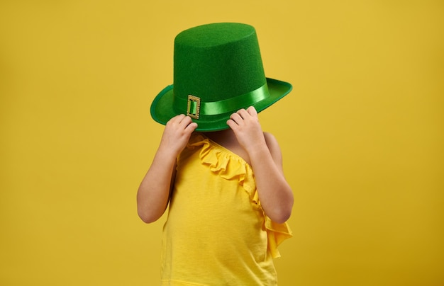 Menina escondendo o rosto sob um chapéu verde de duende irlandês