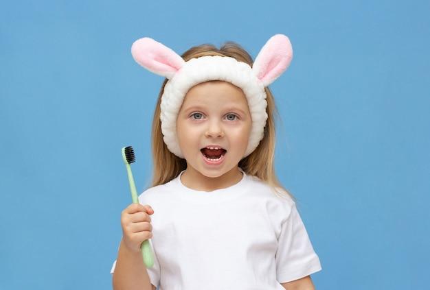 Menina escovando os dentes e usar orelhas de coelho em um fundo azul.