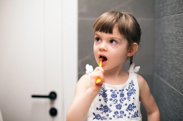 Menina escovando os dentes em um banheiro