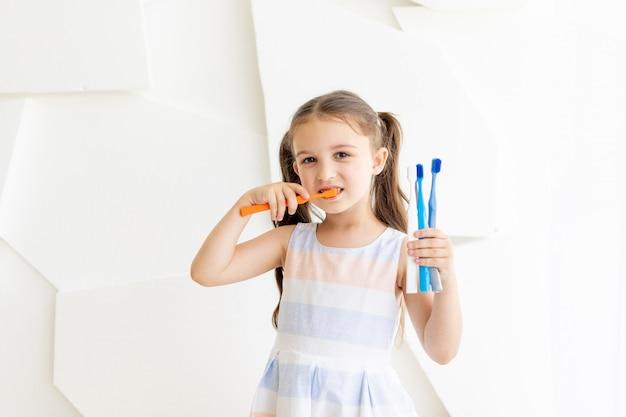 Menina escovando os dentes segurando escovas de dentes, lugar para texto, dentes saudáveis