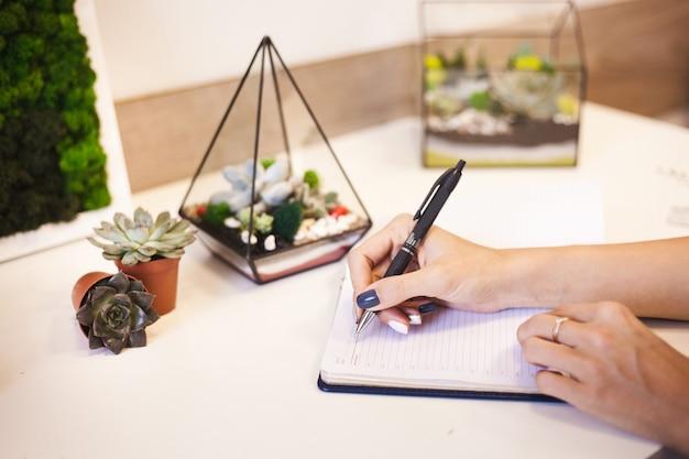Menina escreve em um planador, diário, planos para o ano, interior com formas de vidro para flores, mesa de escrita