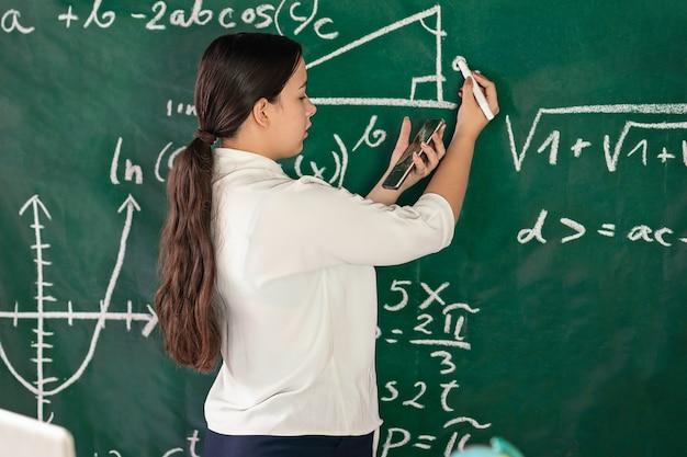 Menina escreve exemplos matemáticos no conselho escolar e resolve um problema de geometria