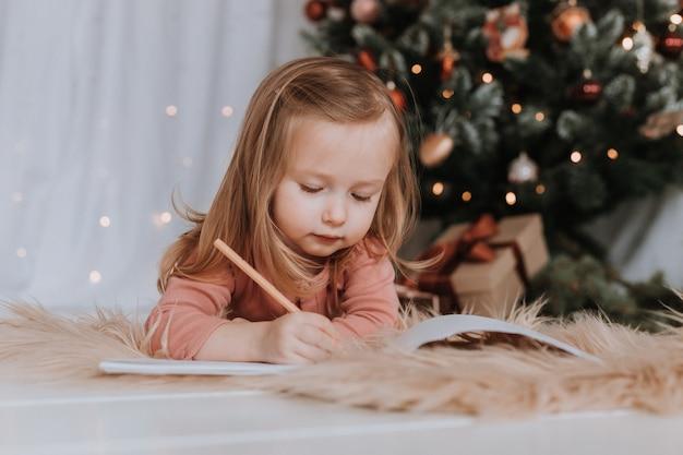 Menina escreve uma carta para o papai noel milagre de natal, árvore de natal, conceito de inverno