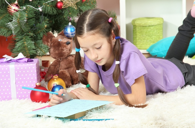 Menina escrevendo carta para o papai noel perto da árvore de natal