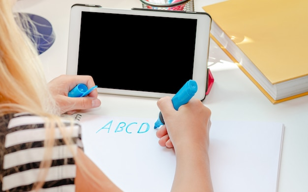 Menina escrevendo cartas na frente do tablet com tela preta vazia. conceito de aprendizagem de inglês online