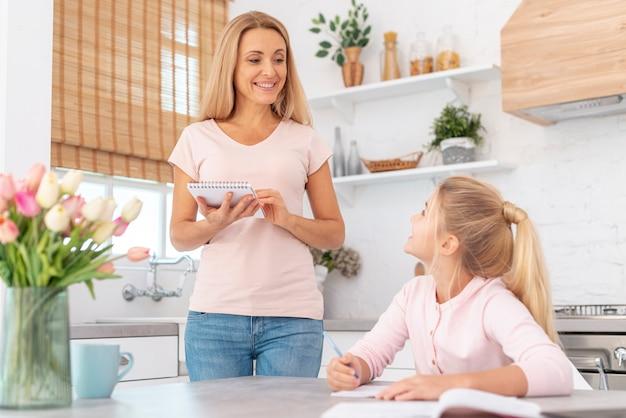 Menina escrevendo dever de casa supervisionado pela mãe