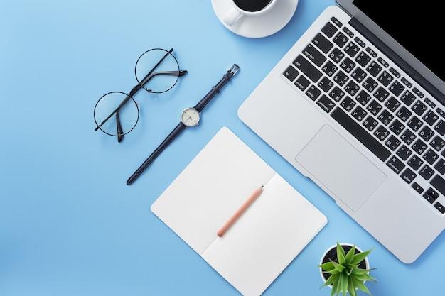 Menina escrevendo em um livro branco aberto ou contabilidade em uma mesa azul clara limpa mínima com laptop e acessórios, espaço de cópia, postura plana, vista superior, simulação