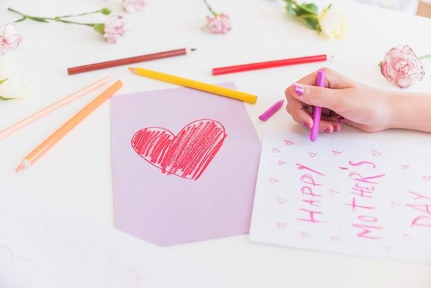 Menina escrevendo feliz dia das mães na folha de papel