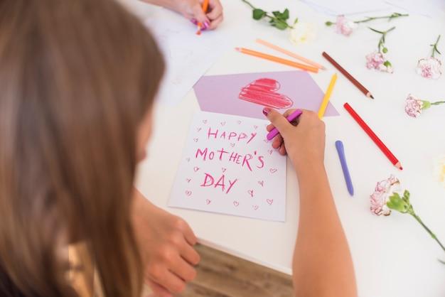 Menina escrevendo feliz dia das mães no papel