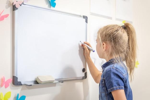 Menina escrevendo na lousa vazia com uma caneta, aprendizagem, educação e volta ao conceito de escola