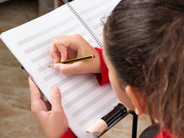 Menina escrevendo notas musicais na pauta