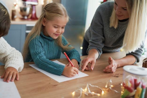 Menina escrevendo uma carta para o papai noel com a mãe
