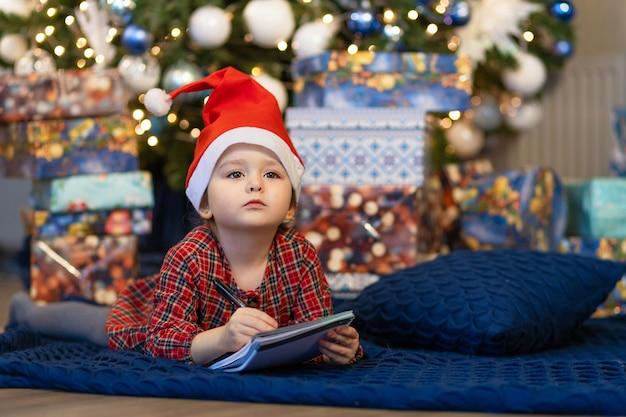 Menina, escrevendo uma carta para o papai noel. criança sonha perto da árvore de natal sobre desejo, presente no ano novo