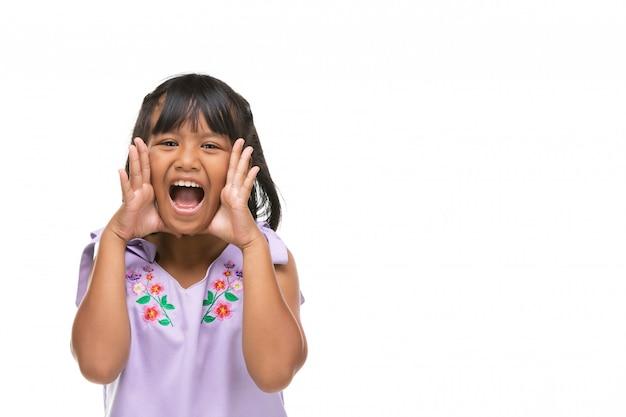 Menina escura asiática bonito que faz uma emoção engraçada na cara.