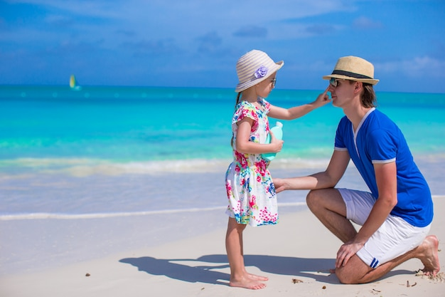 Menina esfrega protetor solar no nariz do pai dela