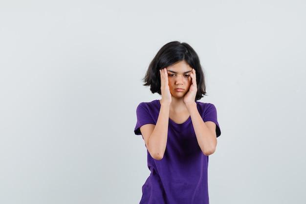 Menina esfregando as têmporas na camiseta e parecendo cansada.