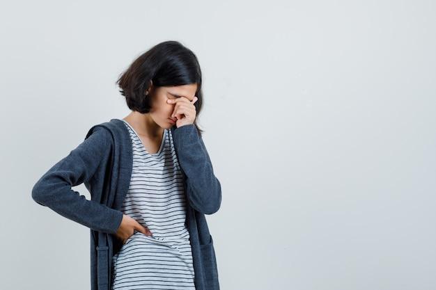Menina esfregando os olhos e o nariz na camiseta, jaqueta e parecendo cansada
