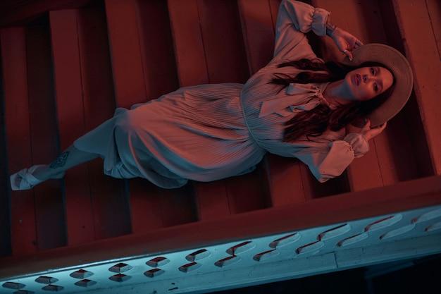 Menina esguia em um vestido e um chapéu deitada em uma escada de madeira, tirando fotos de fotos modernas para uma loja de roupas.