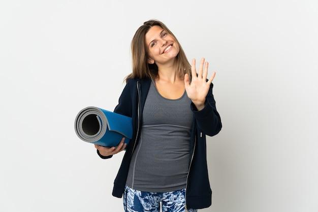 Menina eslovaca indo para aulas de ioga isolada no fundo branco, contando cinco com os dedos