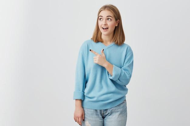 Menina espantada com a boca aberta, olhando com os olhos escuros de lado apontando com o dedo indicador e anunciando algo. jovem mulher posando com espaço de cópia de texto ou promoção