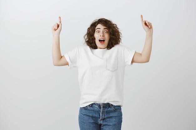 Menina espantada e animada com uma camiseta branca apontando os dedos para cima, arfando e perplexa