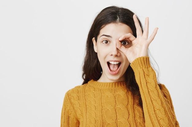 Menina espantada e animada mostrando zero, olhando através de um gesto de ok. descontos fantásticos